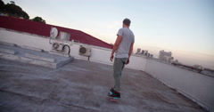 Hipster man on a Skateboard on the rooftop Stock Footage