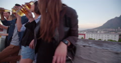 Young adult friends drinking on a summer rooftop party Stock Footage
