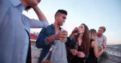 Young adult friends chatting on a summer rooftop party Stock Footage