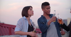 Teens celebrating a funny rooftop party at sunset - stock footage