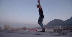 Hipster Girl balancing on the edge of rooftop - stock footage