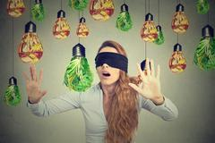 Blindfolded young woman walking through light bulbs shaped as junk food and g Stock Photos