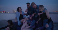 Hipster friends dancing and talking on a rooftop party - stock footage