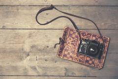 retro camera with vintage photo album on wooden background - stock photo