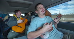 Two guys are playing their guitars in the van when the vehicle is moving Stock Footage