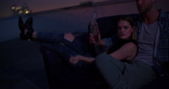 Happy young couple dating on a sofa on the rooftop - stock footage