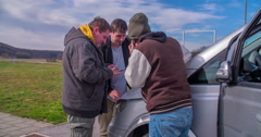 One of the guys is talking on the phone and the other two are checking the map Stock Footage
