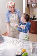 Little girl is helping her mother to cook Stock Photos