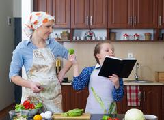 Little girl is teaching her mother to cook Stock Photos