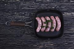 Raw sausages on a  pan,  wooden background Stock Photos