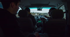 Three guys are driving in a car and one of them offers some biscuits to eat Stock Footage