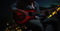 Young adult playing guitar on rooftop with Skyline background - stock footage