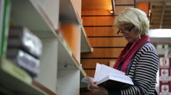 Blonde Woman browsing books in a bookstore Stock Footage
