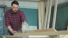 Carpenter in protective goggles sawing boards in the workshop Stock Footage