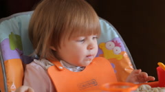 Cute Baby Girl Sitting In The Highchair And Eats Stock Footage