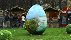 A huge Easter Art-egg in the Prague Old Town lies on a grass with passers. Stock Footage