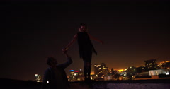 Man is holding hand with girlfriend who is balancing on rooftop edge Stock Footage