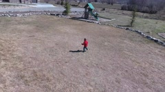 Aerial shot of a little boy running across the grass Stock Footage