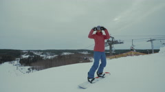 Woman snowboarder ride down ski slope - stock footage