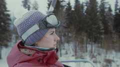 Ski resort, woman ride up on riding lift - stock footage