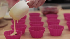 Cupcake batter being poured into cupcake form. Stock Footage