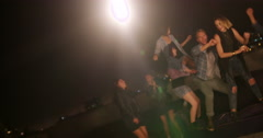 Young adults singing and dancing on a rooftop party Stock Footage