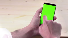 man hand using a smart phone with chroma key on wood background, green screen - stock footage