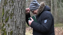 Sorrowful man with Bible and rosary crying near tree Stock Footage