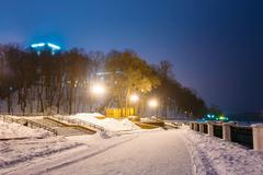 Snowy city park in light of lanterns at evening in Gomel, Belaru Stock Photos