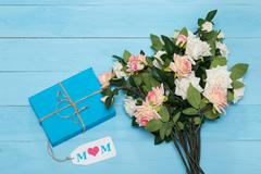 Mothers day card and  roses on blue background with gift - stock photo