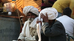 Old indian man wraps the fabric produced as a traditional turban Stock Footage