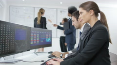 4K Group of financial brokers working together, watching world markets - stock footage