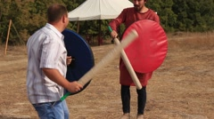 Two Men are Fighting with the Truncheons and Shields at the Historical Festival Stock Footage