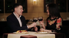 smiling couple clinking glasses of wine during lunch at the restaurant - stock footage