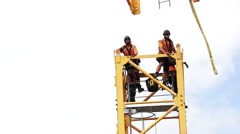 Builders assemble a construction tower crane - stock footage