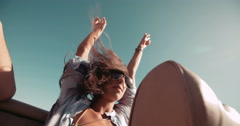 Young adult hippie girl with raised arms on a convertible car - stock footage