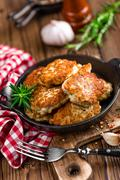 meat cutlets in frying pan on wooden rustic table - stock photo