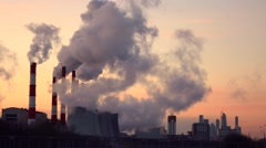 Steaming cooling towers and smoking industrial stacks against gradient sky. 4K - stock footage
