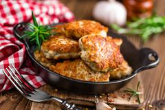 Meat cutlets in frying pan on wooden rustic table Stock Photos