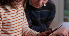 4k, Big brother watches as his little sister is busy using her digital tablet. - stock footage