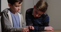 4k, Two young boys playing online games on a digital touchscreen tablet. - stock footage