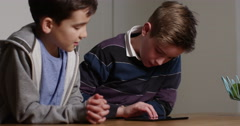 4k, Two young boys playing online games on a digital touchscreen tablet. Stock Footage