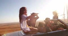 Group of happy young people on convertible car road trip - stock footage