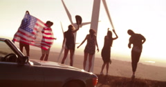 Carefree Friends road tripping to wind farm carring American flag Stock Footage