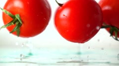 Red ripe tomatoes hit wet glass surface with splashes and rebound. Slow motion Stock Footage