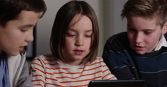 4k, Elder brothers watch their little sister play games on a digital tablet. Slo Stock Footage
