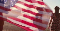 Attractive young adult woman holds an American flag - stock footage