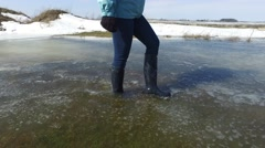 4k closeup of women's boots walking water and slush Stock Footage