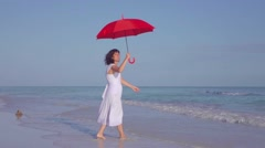 Elegant Woman In White Dress Walking Beach With Red Umbrella - stock footage