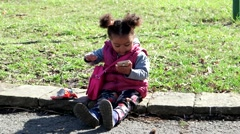 Little curly black girl sitting on the lawn watching a cartoon on smart phone. - stock footage